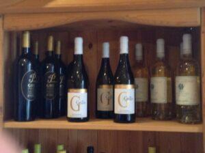 Nahaufnahme des obersten Bereiches eines Regals mit Weinflaschen von Grillo