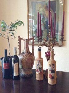 Verschiedene Weinfalschen und ein Weinkrug auf einem Holztisch