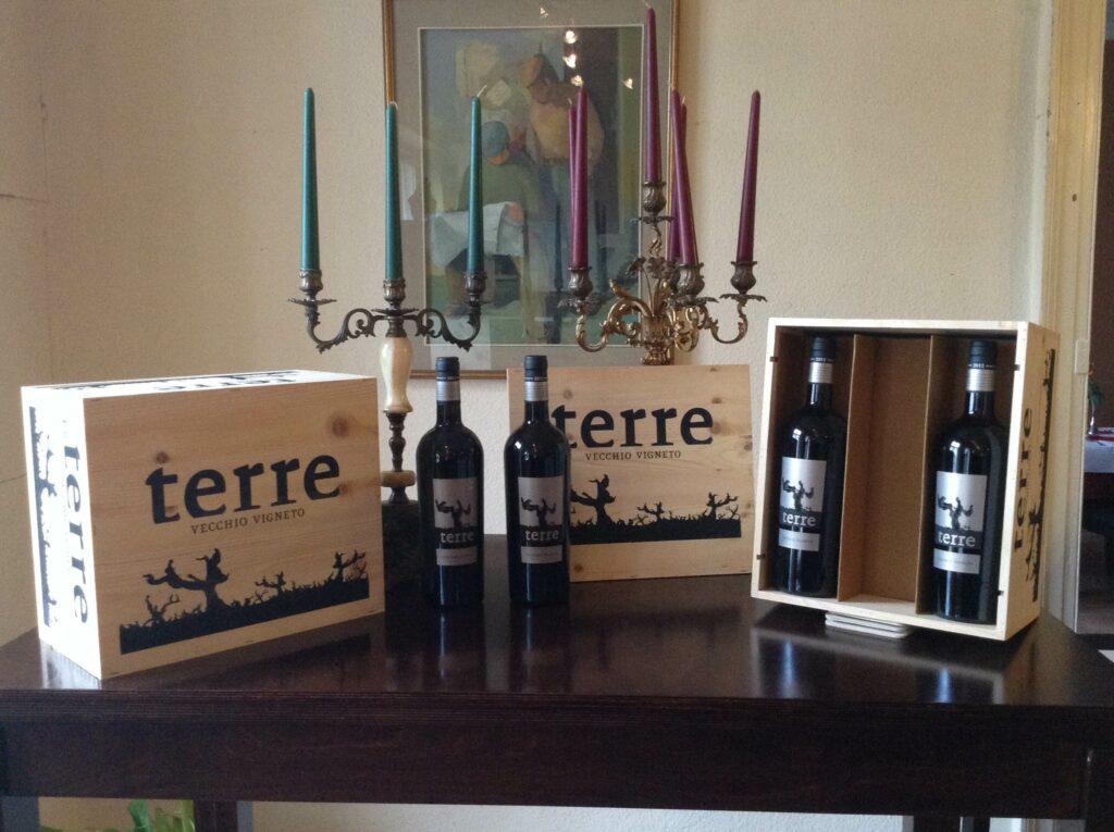 terre Weinflaschen und Holzboxen auf einem Holztisch vor zwei Kerzenständern